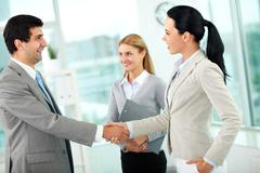 portrait of successful partners handshaking after signing contract - stock photo