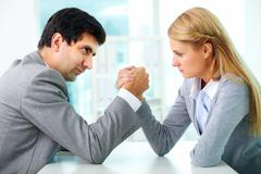 man and woman in arm wrestling gesture on working table during meeting - stock photo