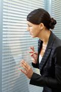 Image of puzzled businesswoman looking through jalousie in office Stock Photos