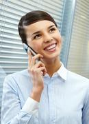 image of young pretty secretary talking by cellular phone in office - stock photo