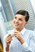 Image of young pretty secretary holding cup of coffee Stock Photos