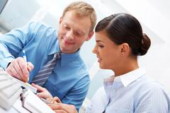 manager showing plans to his female subordinate - stock photo