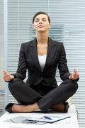 Image of young employer on workplace and meditating Stock Photos