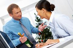 portrait of young businessman with bottle of champagne and two flutes offering h - stock photo