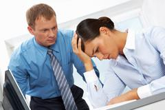 portrait of young employee having trouble or headache with her boss at backgroun - stock photo
