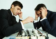 Image of businessman making move while playing chess with his rival in front of Stock Photos