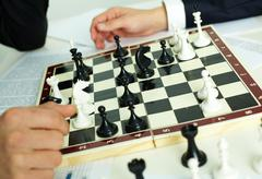 image of chess figures on chessboard with human hands near by - stock photo