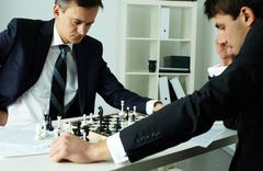 Image of two businessmen looking at chessboard while playing chess Stock Photos