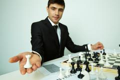 Image of successful businessman looking at camera while showing rook figure Stock Photos