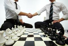 Stock Photo of four rows of chess figures on chess board with two men handshaking on background
