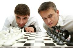 Two men looking at chess figures on chess board Stock Photos