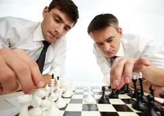 two men looking at chess figures while making their move - stock photo