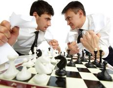two men with papers looking at each other aggressively while playing chess - stock photo