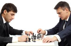 image of two businessmen thinking of move while playing chess - stock photo