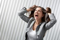 A depressed businesswoman screaming and tousling her hair Stock Photos