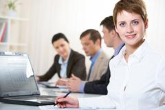 image of pretty blue-eyed female looking at camera in working environment - stock photo