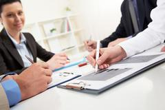 close-up of business person hand over document in working environment - stock photo