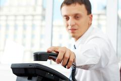 a manager picking up telephone receiver - stock photo