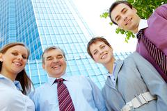 below angle of several successful partners looking at camera with smiles - stock photo