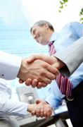 Vertical image of rows of partners handshaking outdoors on background of modern Stock Photos
