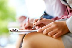 close-up of hands with pens and legs in line outdoor - stock photo