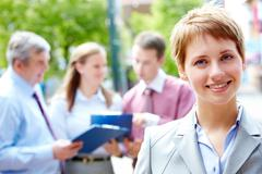 portrait of pretty employee smiling at camera in a natural environment - stock photo