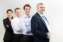 portrait of a business team of four looking at camera and smiling - stock photo