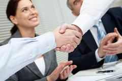 Close-up of two shaking hands against business team Stock Photos