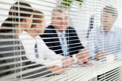 business team sitting behind blinds - stock photo