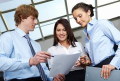 photo of confident employees discussing at meeting - stock photo