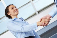 businesswoman shaking hands with some man - stock photo