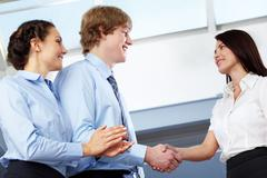 image of business partners making an agreement with woman clapping her hands nea - stock photo