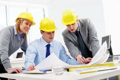 Three architects sitting at table and looking at a project Stock Photos