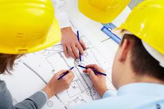 Three architects correcting a construction plan Stock Photos