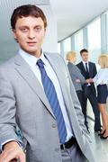 portrait of a young confident businessman with working team on background - stock photo