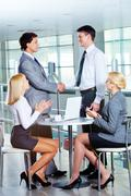 portrait of two businessmen handshaking while females applauding - stock photo