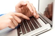 Stock Photo of close-up of male hand over laptop keyboard while the other one hiding forefinger