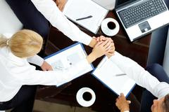 Close-up  of co-workers making pile of hands at meeting Stock Photos