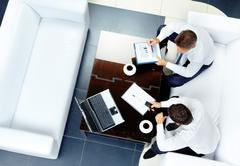 Image of two businessmen sitting on a white sofa Stock Photos