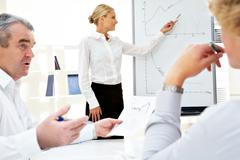 Image of successful businesswoman standing by whiteboard while her colleagues li Stock Photos