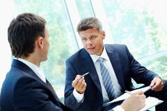 Image of smart boss explaining to colleague business idea Stock Photos