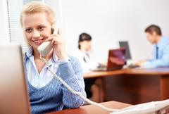 a young woman secretary talking on the phone - stock photo