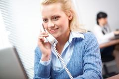a young woman receptionist with a telephone receiver - stock photo