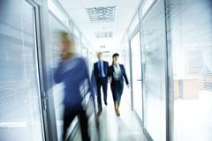 Business people walking in the office corridor Stock Photos