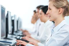 Close-up of a businesswoman working on computer among her colleagues Stock Photos