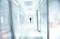 A businessman walking in the office corridor Stock Photos