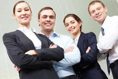 portrait of four smiling confident business people - stock photo