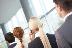 rear view of business woman calling among her colleagues - stock photo