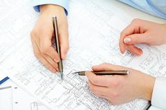 Close-up of engineers hands with pens over blueprints with sketches of projects Stock Photos