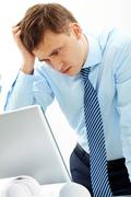 Portrait of serious businessman in front of laptop Stock Photos